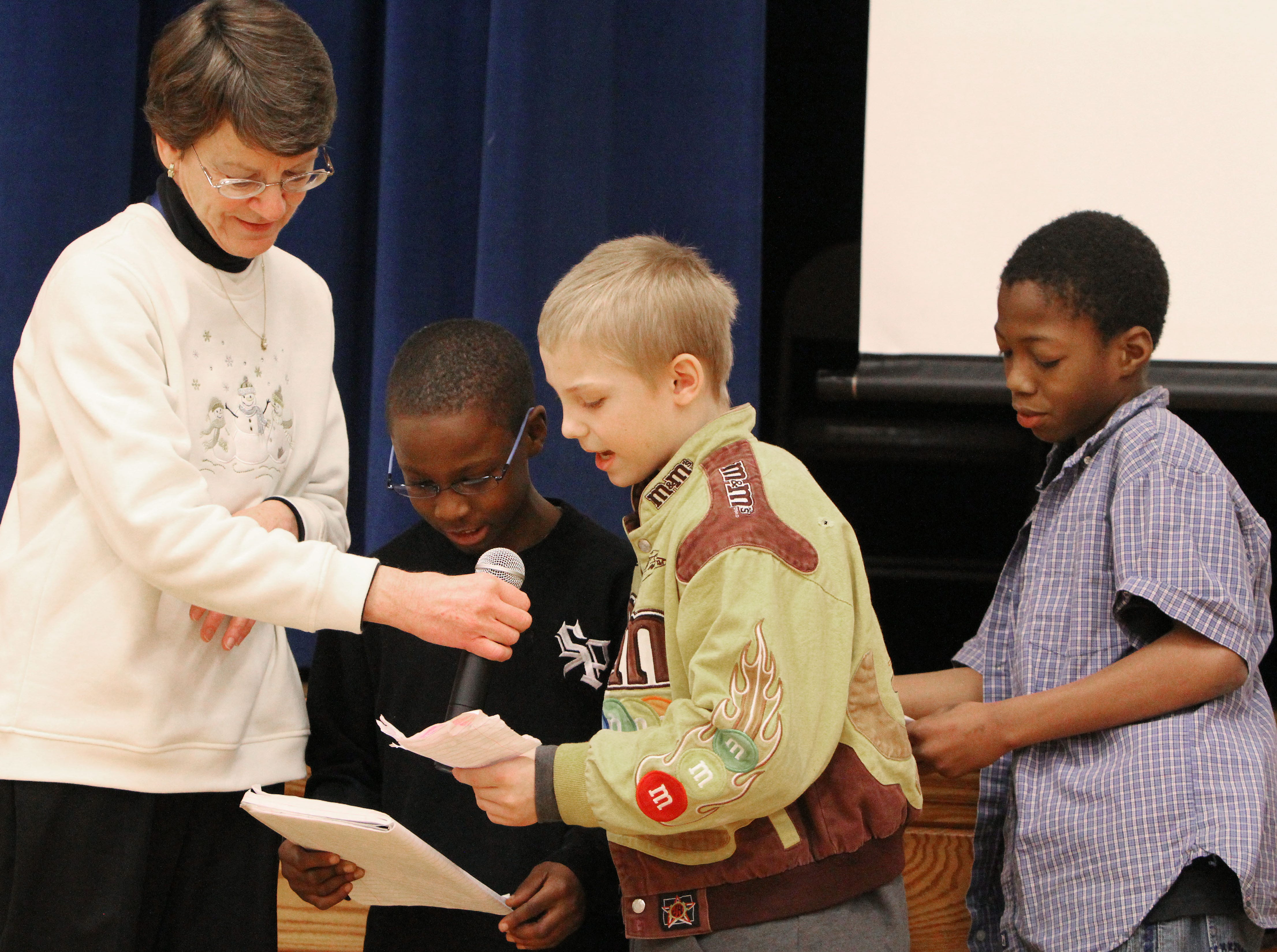 2012: Fassett Elementary School music teacher Ruth Bruning holds the microphone as fourth-graders, from left, Jayzell McCoy, Stephen Lattimer and Andre Murphy read their haiku honoring Martin Luther King, Jr, during the Martin Luther King, Jr. assembly Friday afternoon.