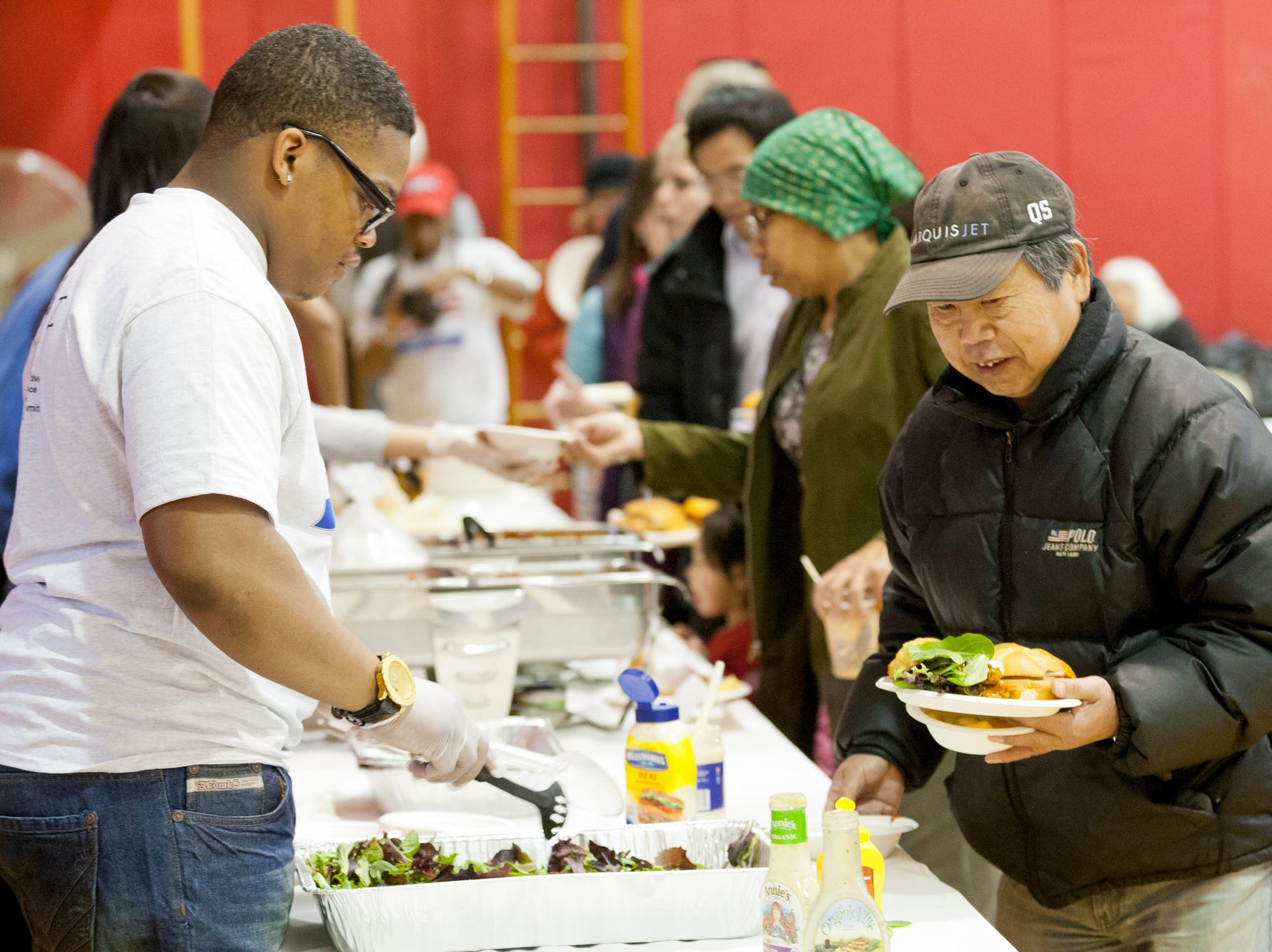 2014: Cornell University freshman Anthony Halmon, of Chicago, left, volunteers his time serving salad, as Chao Cheng of Ithaca, right, makes his way through the food line Monday at the Martin Luther King Jr. luncheon held in the Beverly J. Martin School gym.