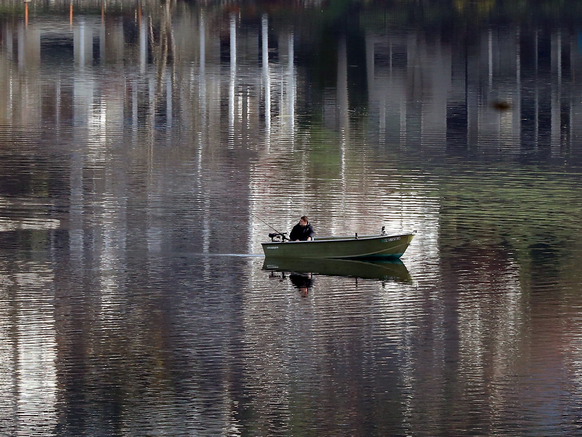 An angler in a small fishing boat moves through the reflections on Kitsap Lake in Bremerton on Tuesday, January 15, 2019.