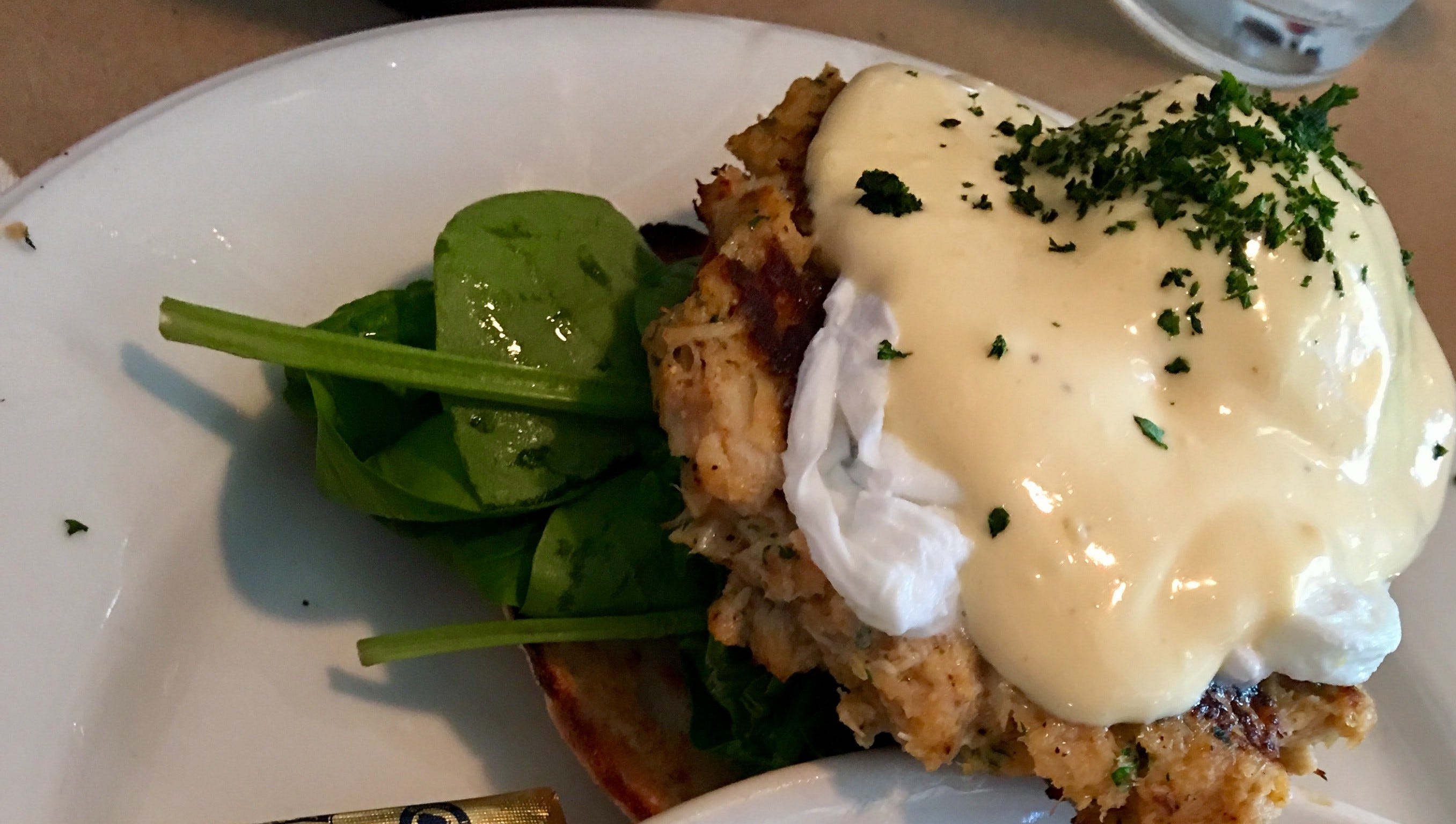 The crab cake eggs benedict at Too Cool Cafe came...