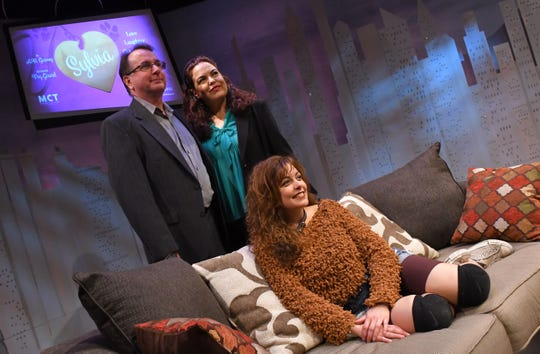 Sylvia, a comedy about a man who finds a labradoodle dog with the name Sylvia in a park. This scene shows Jessica Foix as Sylvia, on the couch, with Mark Blackledge as Greg and Shane Frampton as Kate. The play contains some crude language.