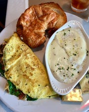 One Too Cool Cafe guest ordered a make-your-own omelet with spinach, mushrooms and cheese, plus grits topped with provolone cheese and a croissant.