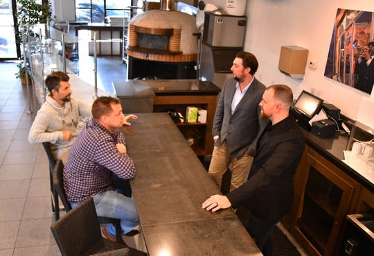 (Left to right) Ember & Oak co-owners Mike Koeppel and Donald Spielman chat near their wood-fired oven with Kevin Andersen, co-owner and executive chef, and Andrew Addleman, chef de cuisine.