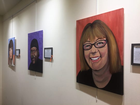 """Portraits line a gallery wall at the """"Faces of Cancer"""" exhibit in Cherry Hill's library."""