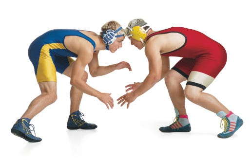 two teenage caucasian male wrestlers from opposing teams face off at the beginning of a match