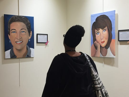 """A patron views portraits in """"Faces of Cancer"""" at Cherry Hill's library."""
