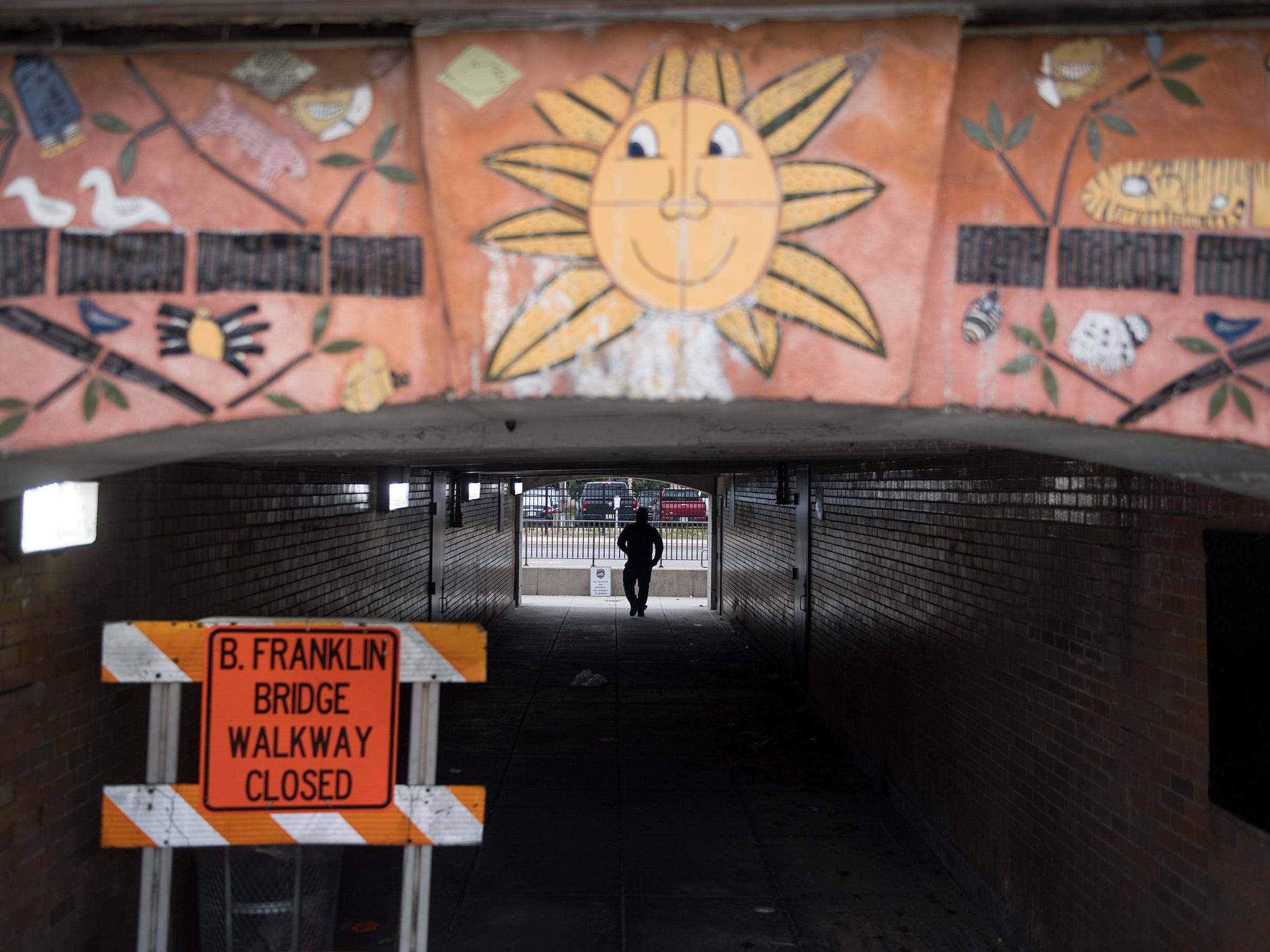 A pedestrian walks through a Benjamin Franklin Bridge pedestrian  access tunnel at 5th Street as construction continues on a bridge pedestrian and bicycle ramp on the other side of the tunnel Monday, Jan. 7, 2019 in Camden, N.J.