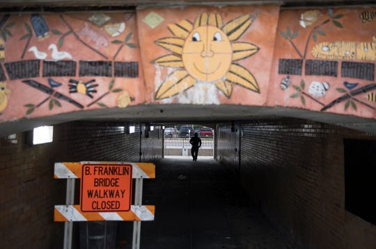 A pedestrian walks through a Benjamin Franklin Bridge pedestrian access tunnel at N. 5th Streetin Camden as construction continues on a bridge pedestrian and bicycle ramp on the other side of the tunnel.
