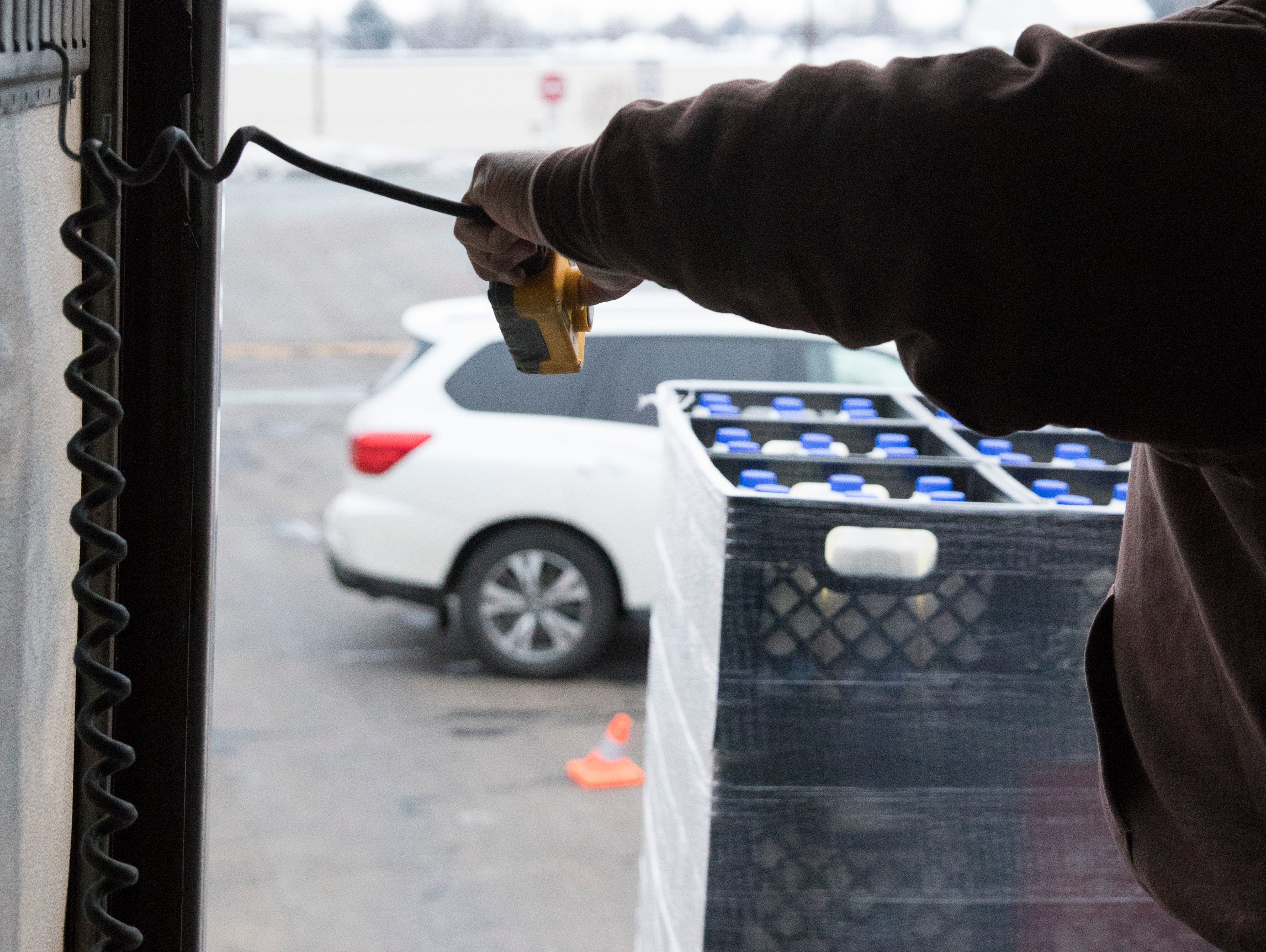 Von Davis from the Mid-Ohio Food bank uses a remote to lower the donated milk to volunteers as the Mobile Market gets ready to serve Ross County residents on Jan. 15, 2019.