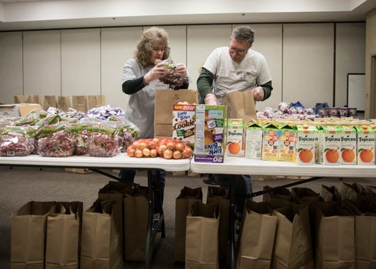 Volunteers Sonja Hines, left, and Martin Frey put together bags of food for those who attend the Hope Clinic during the Mobile Market Monday night in Chillicothe, Ohio.