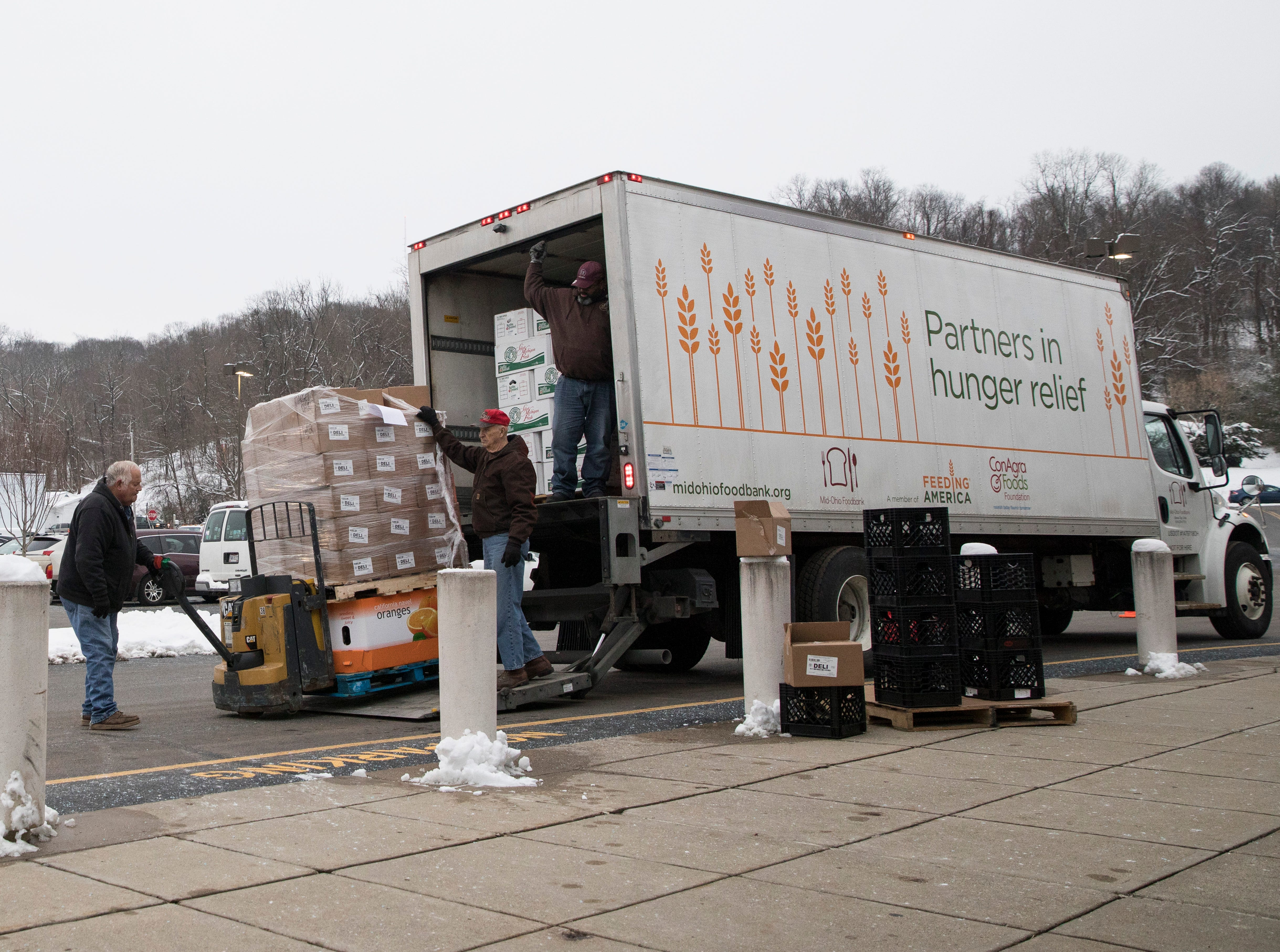 Gerald Gallagher, left, helps Randall Bland transport food from the Mid-Ohio Valley Food Bank truck to those waiting inside during the Mobile Market in Chillicothe, Ohio.