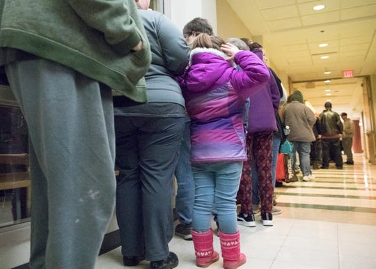 A long line of those waiting to collect food from the Mobile Market fill the long hallway inside the Ross County Job and Family Services building on Jan. 14, 2019. Volunteers for the food bank give up their time every second and fourth Monday of the month to help supply food to residents who are in need.