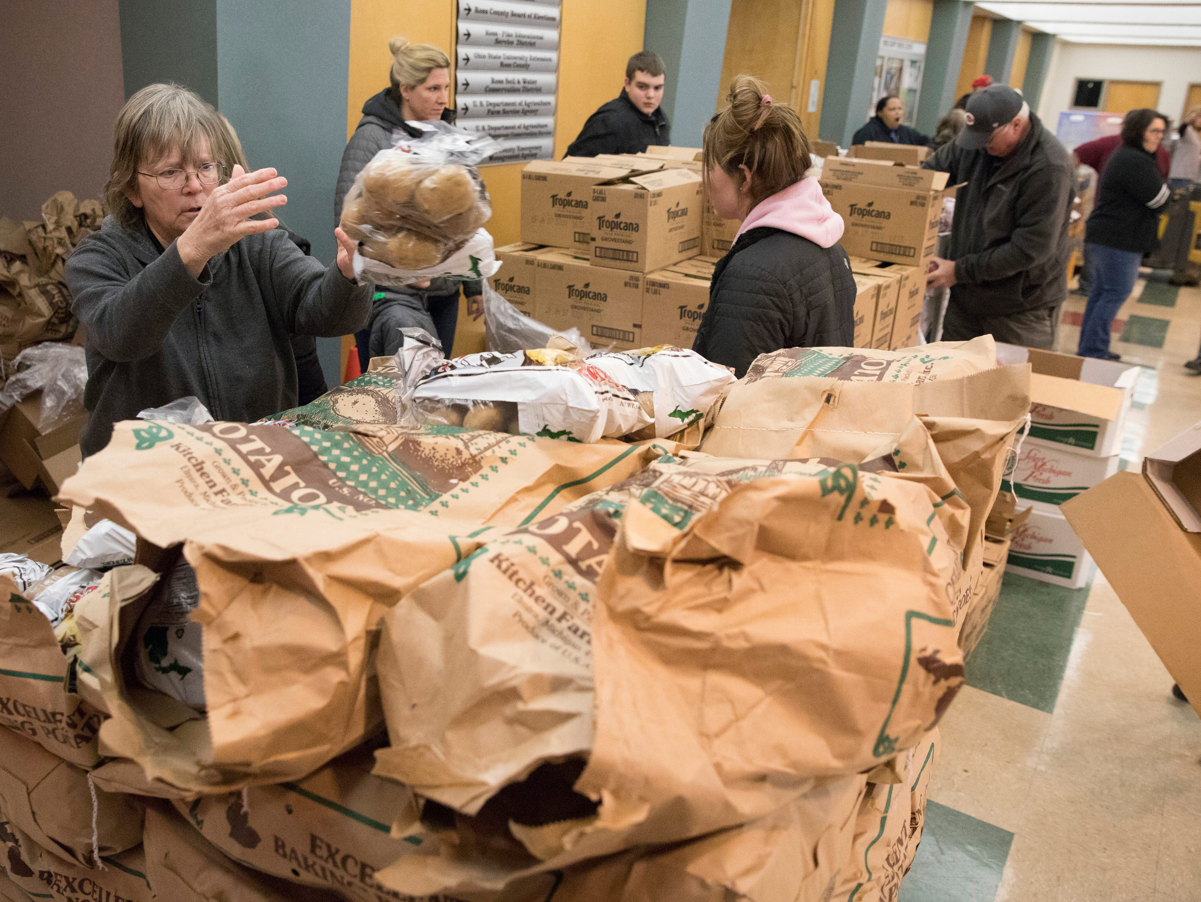 Volunteer Bev Davis sorts through bags of potatoes as she and other volunteers get ready to serve local residents during the Mobile Market at the Ross County Service Center.