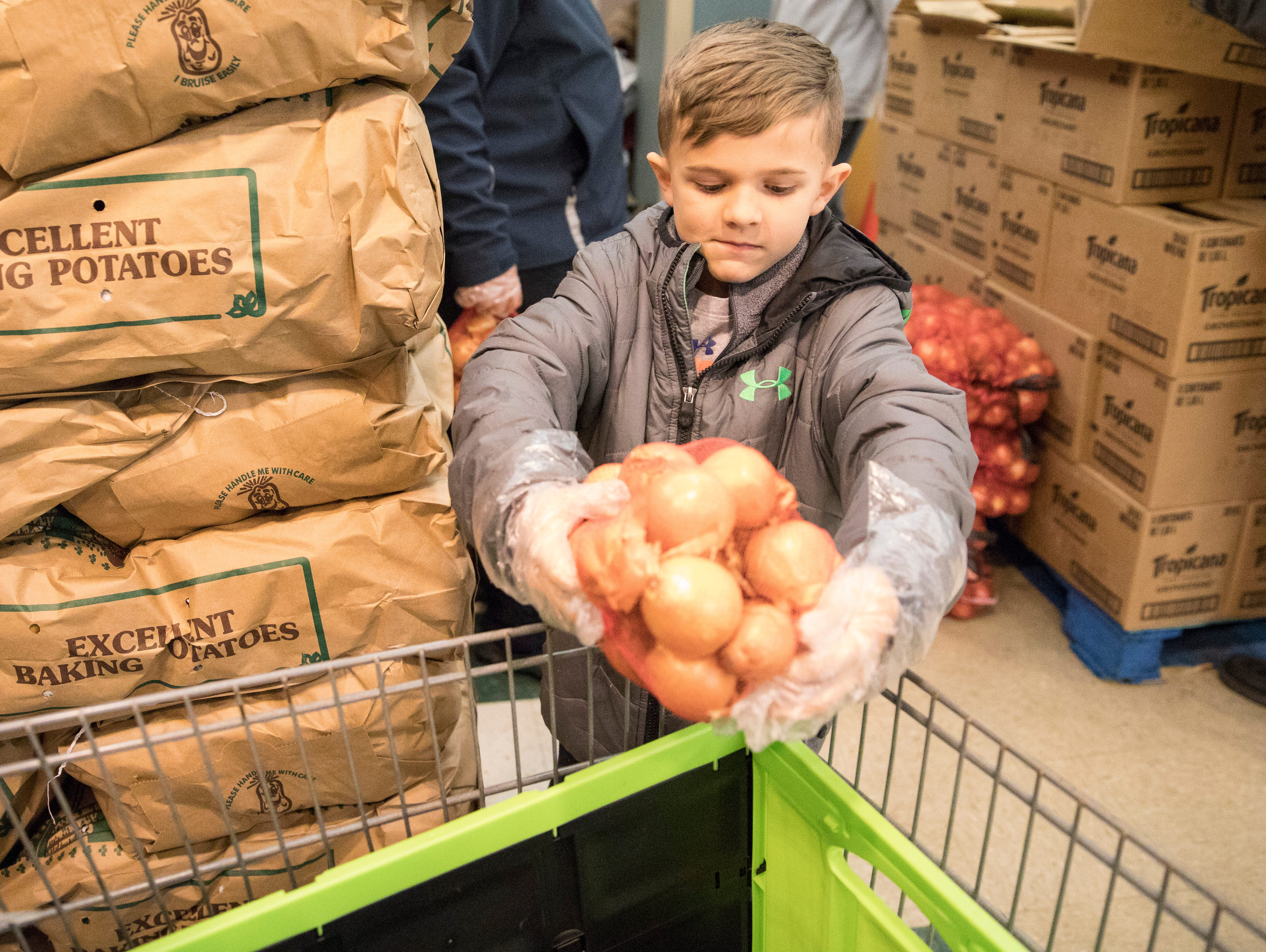Ethan Young, 6, volunteers his time at the Mobile Market  in Chillicothe, Ohio, Monday night.