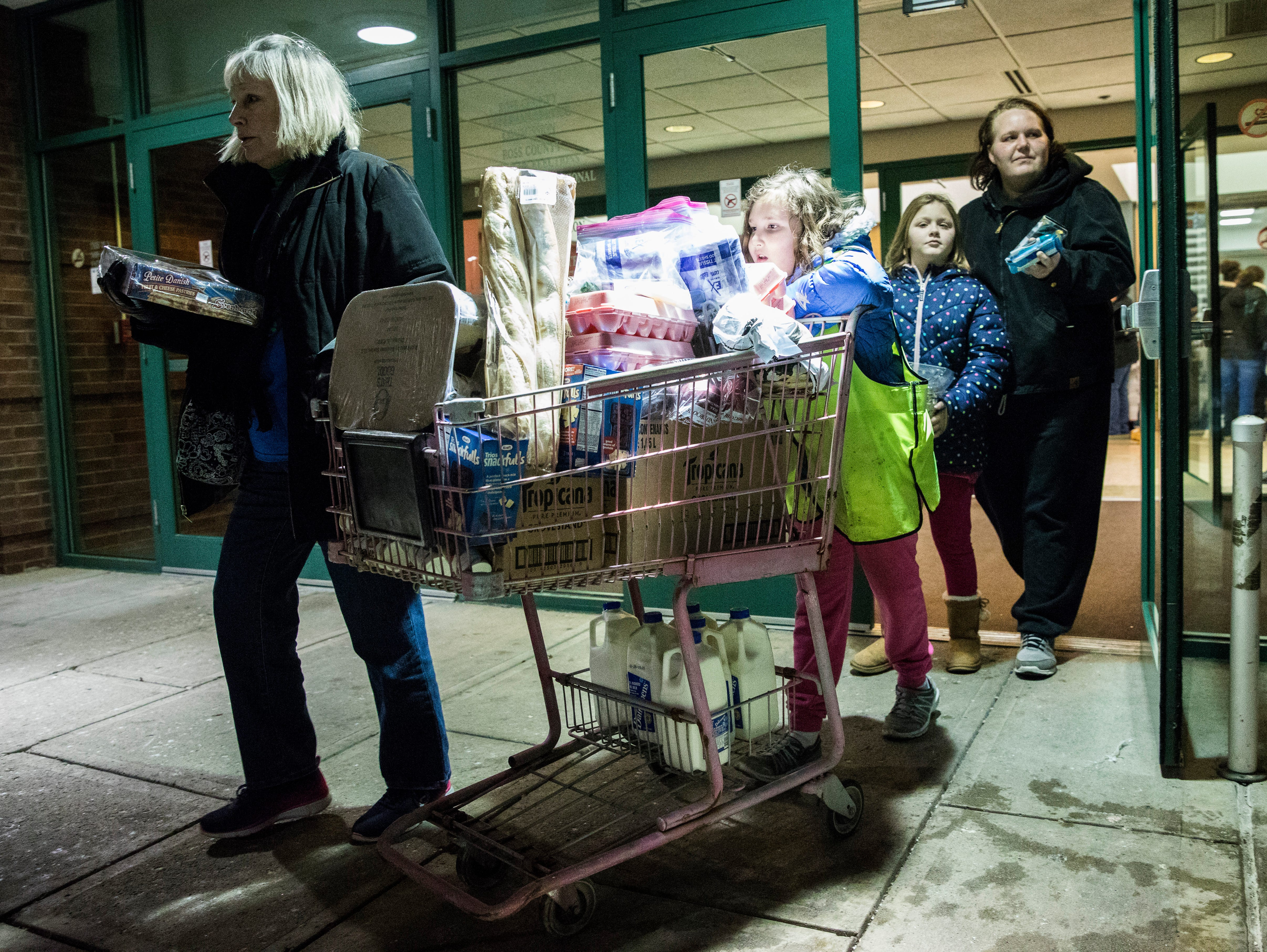 Kelly Ewry and her children leave the Mobile Market with a cart full of food Monday night in Chillicothe, Ohio.