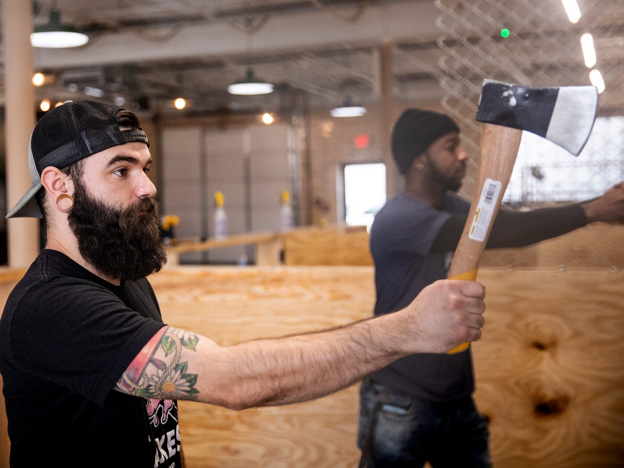 Ryan Bell, a coach at Urban Axes Cincinnati, demonstrates axe throwing at Urban Axes Cincinnati Tuesday, January 15, 2019 at a media preview. Urban Axes offers group bookings, walk-ins and leagues.
