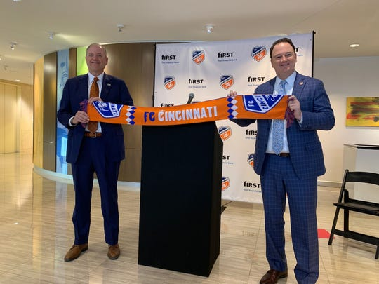 First Financial Bank CEO Archie M Brown Jr. (left) and FC Cincinnati President and General Manager Jeff Berding hold a club scarf after announcing a multi-year deal to make the bank the club its exclusive banking and financial services partner.