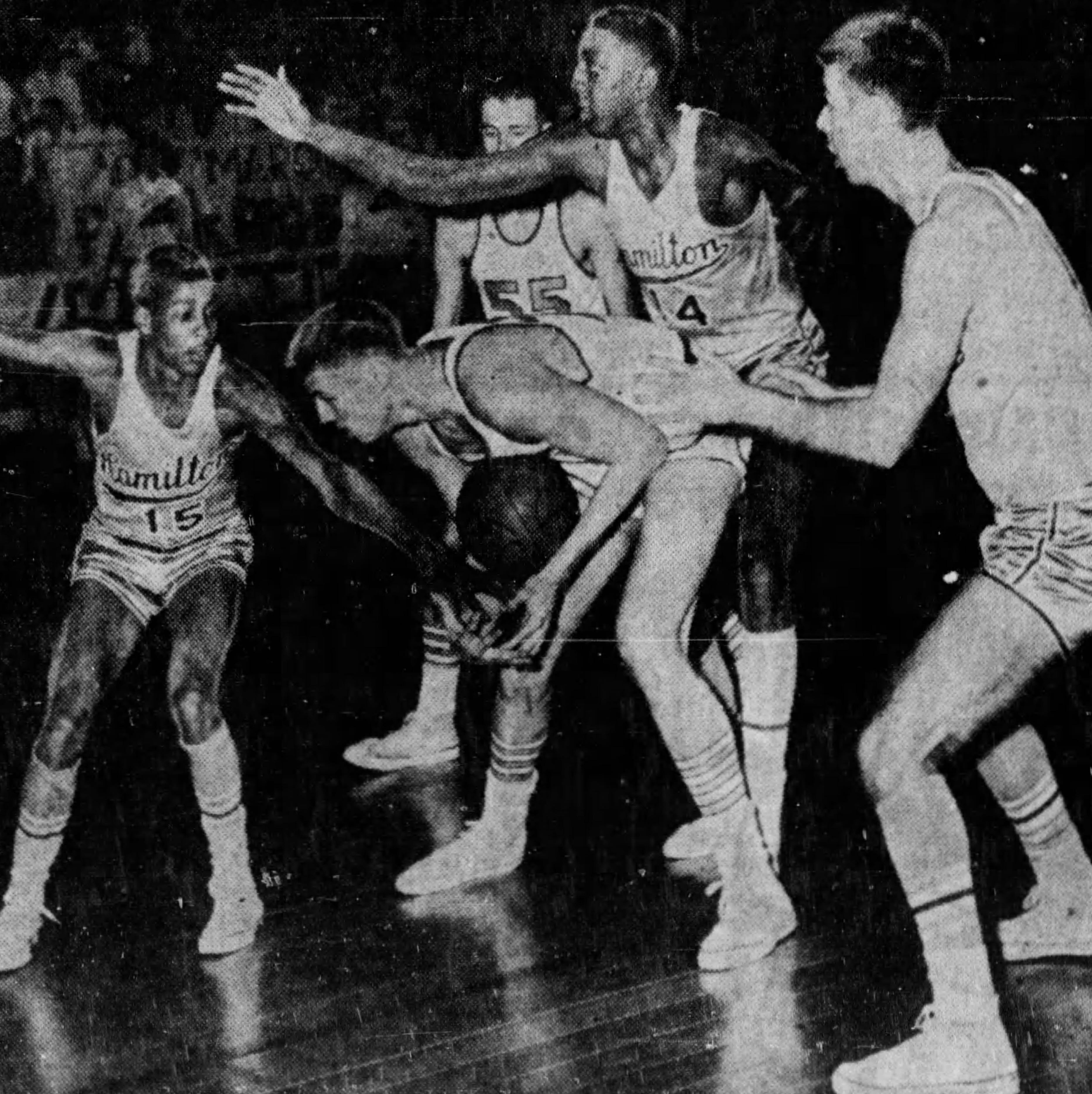 MARCH 14 1954: Ralph Crosthwaite, Western Hills center, found himself well protected by Alex Ellis (14) of Hamilton. Forward Bob Henderson (15) of the Big Blue is on the left while Earl Herzog (55), Maroons forward, watches the play.