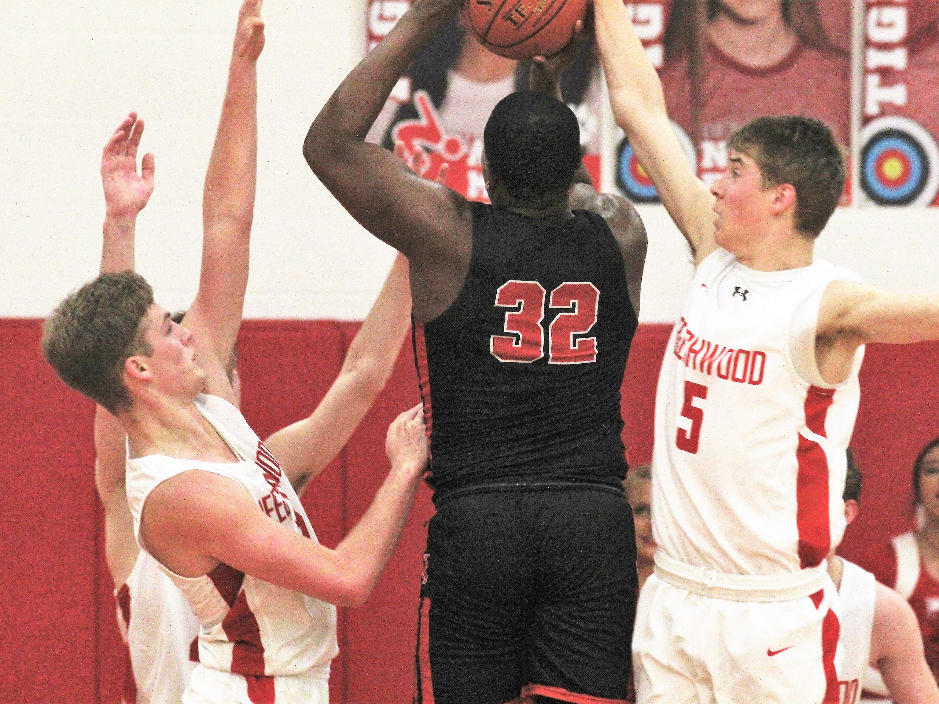 "Newport senior Tahj Harding shoots over Beechwood junior Brandan Hughes, left, and senior Zach Deatherage as Newport defeated Beechwood 53-52 in the first round of the All ""A"" 9th Region boys basketball tournament Jan. 14, 2019 at Beechwood HS, Fort Mitchell KY."