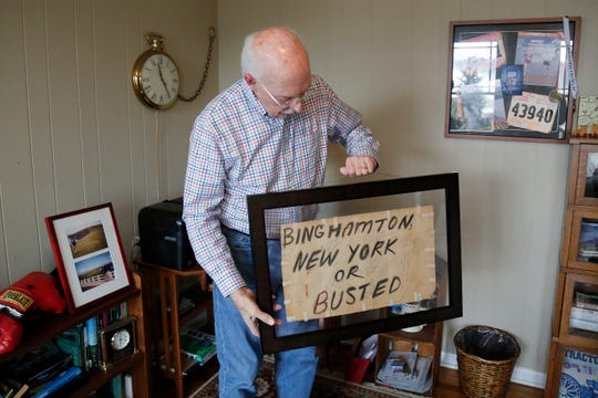 Retired broadcaster Jim Scott holds the sign he drew to hitchhike between New York and Virginia when he considered becoming a priest in his early years of college.