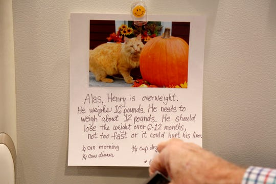 Former broadcaster Jim Scott points to note written by his wife Donna about their overweight cat, Henry, on the refrigerator at his home in Lawrenceburg, Ind., on Thursday, Jan. 10, 2019. Scott retired from radio in 2015 after more than 50 years in the broadcasting business.