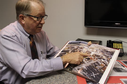 """Clarksville businessman Frank Lott shows an image of the destroyed downtown Clarksville area that was featured in the reprint of the book he helped publish, """"Historic Clarksville 1784-2004."""""""