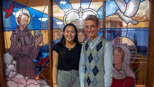 Christina Nguyen, a member of the Class of 2018 at Oak Knoll School in Summit, poses with Creative Arts Director Will Cardell in front of stained-glass window she designed for the school.
