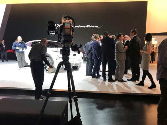 A group gathers on the North American International Auto Show floor Monday, Jan. 14, 2019, at Cobo Center in Detroit.
