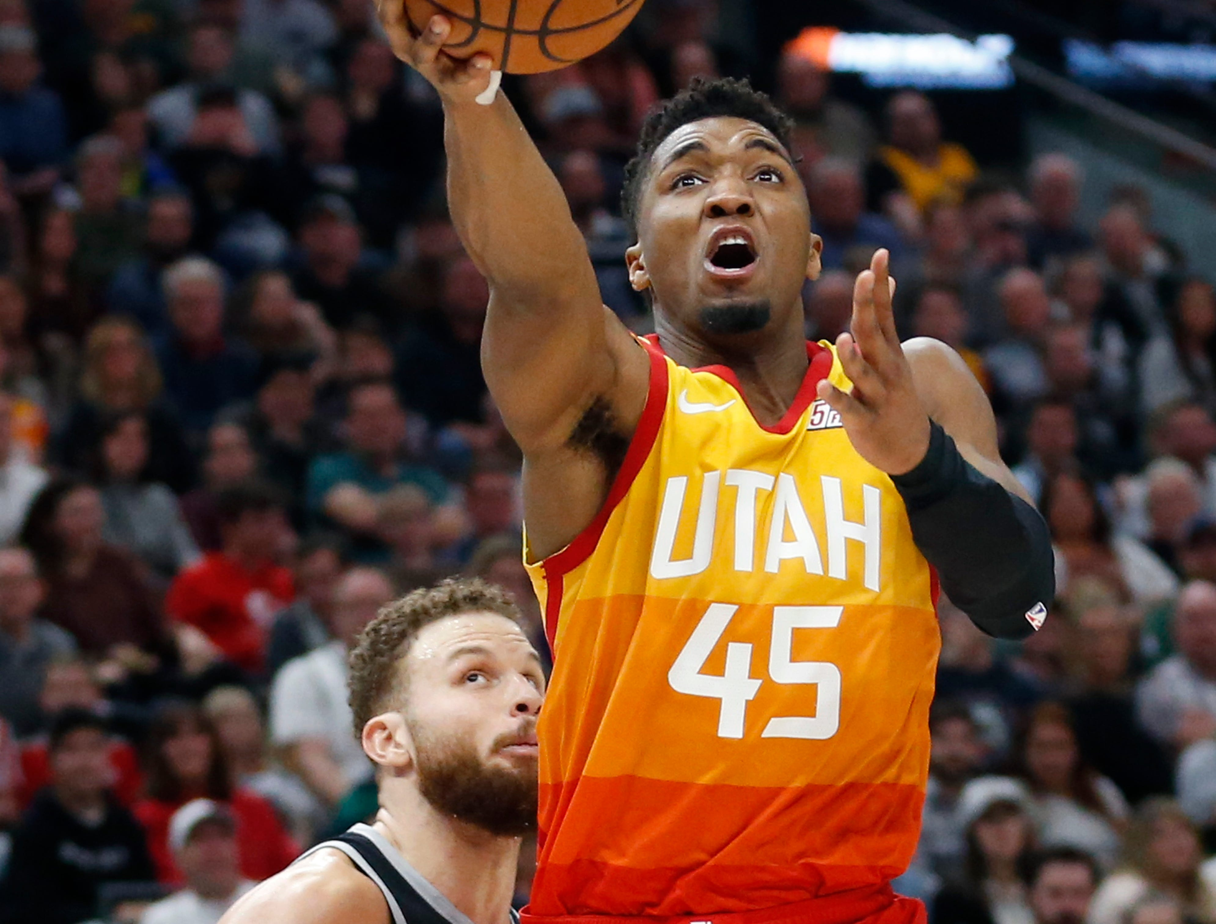 Jazz guard Donovan Mitchell lays up the ball as Pistons forward Blake Griffin, rear, looks on during the second half of the 100-94 loss to the Jazz on Monday, Jan. 14, 2019, in Salt Lake City.