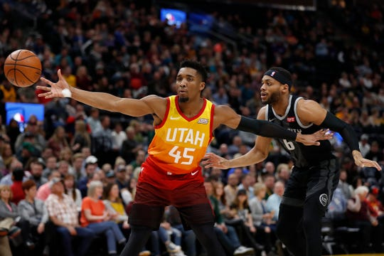Jazz guard Donovan Mitchell receives a pass against Pistons guard Bruce Brown in the first quarter Monday in Salt Lake City.