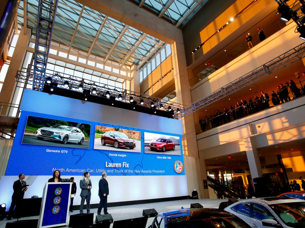 People gather and watch as the North American Car and Truck of the Year are announced during the start of the North American International Auto Show media previews at Cobo Center in Detroit on Monday, January, 14, 2019.