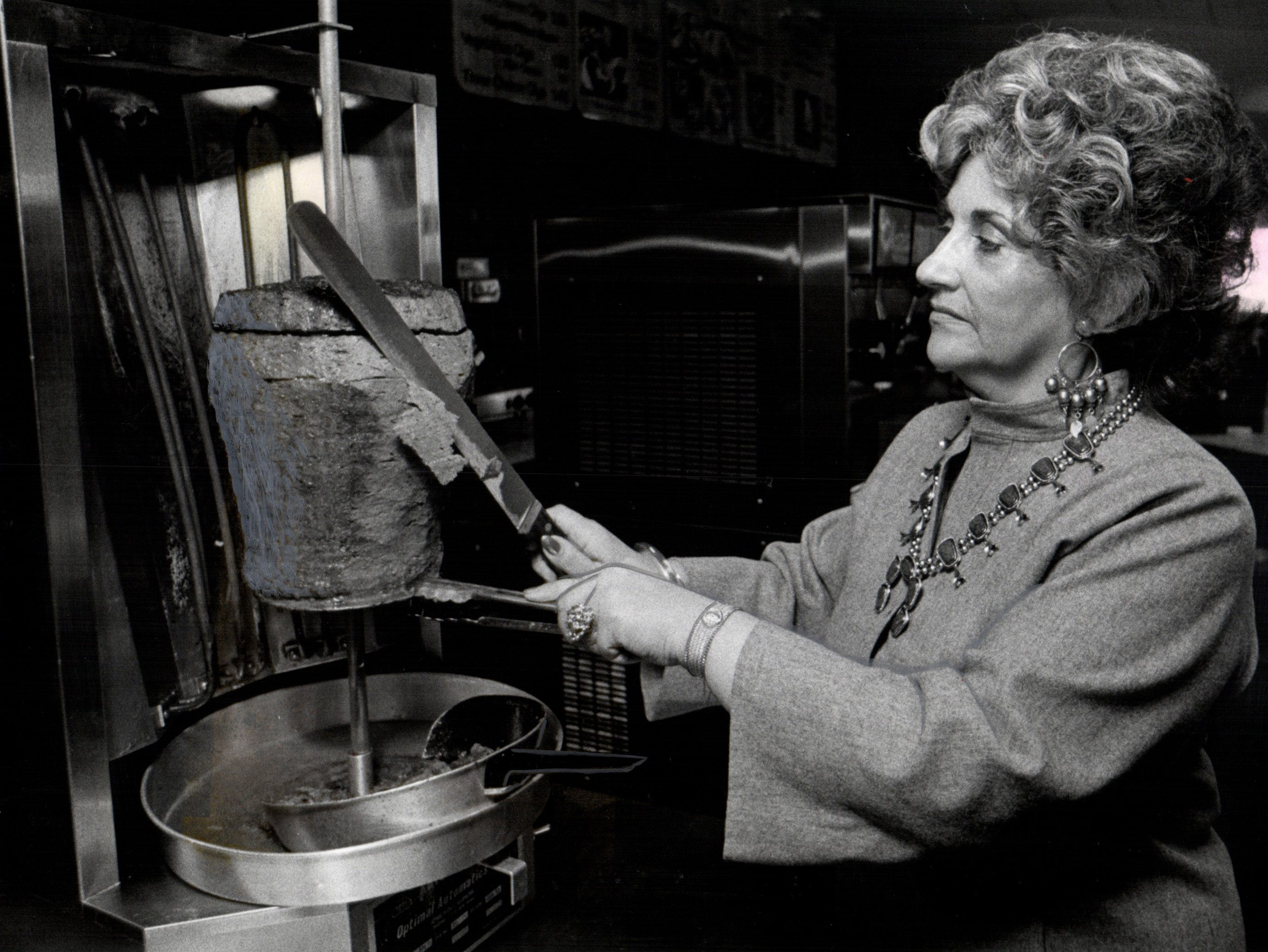 Olga Loizon is photographed carving meat in 1978.