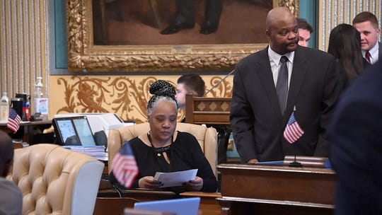Senator Betty Jean Alexander, D-Detroit, reads some papers at her seat on the floor of the Michigan Senate, while Chief of Staff Lamar Lemmons, right, looks on. He coached her through the session.