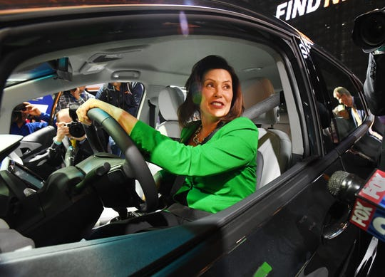 Michigan Governor Gretchen Whitmer gets a feel for the Chevrolet Bolt EV in the General Motors display during a tour of the North American International Auto Show during media preview days at Cobo Center in Detroit, Michigan on January 14, 2019.  (Image by Daniel Mears / The Detroit News)