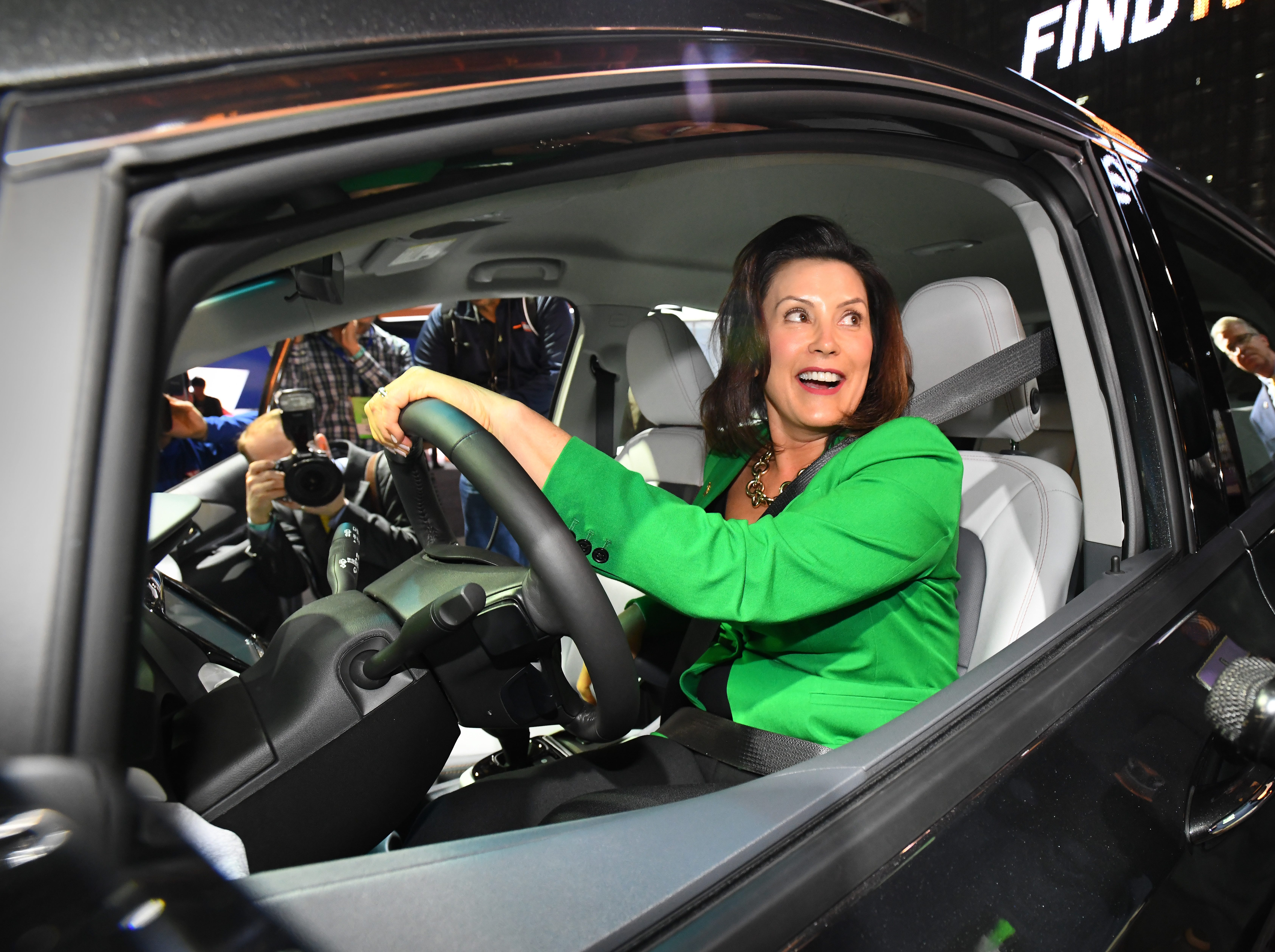 Michigan Governor Gretchen Whitmer gets a feel for the Chevrolet Bolt EV in the General Motors display during a tour of the North American International Auto Show.