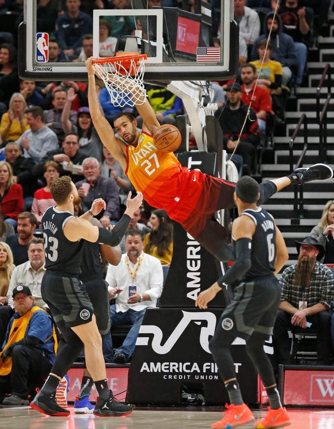 Utah Jazz center Rudy Gobert (27) dunks on Detroit Pistons' Blake Griffin (23) and Bruce Brown (6) during the first half of their game, Monday night, January 14, 2019, in Salt Lake City.
