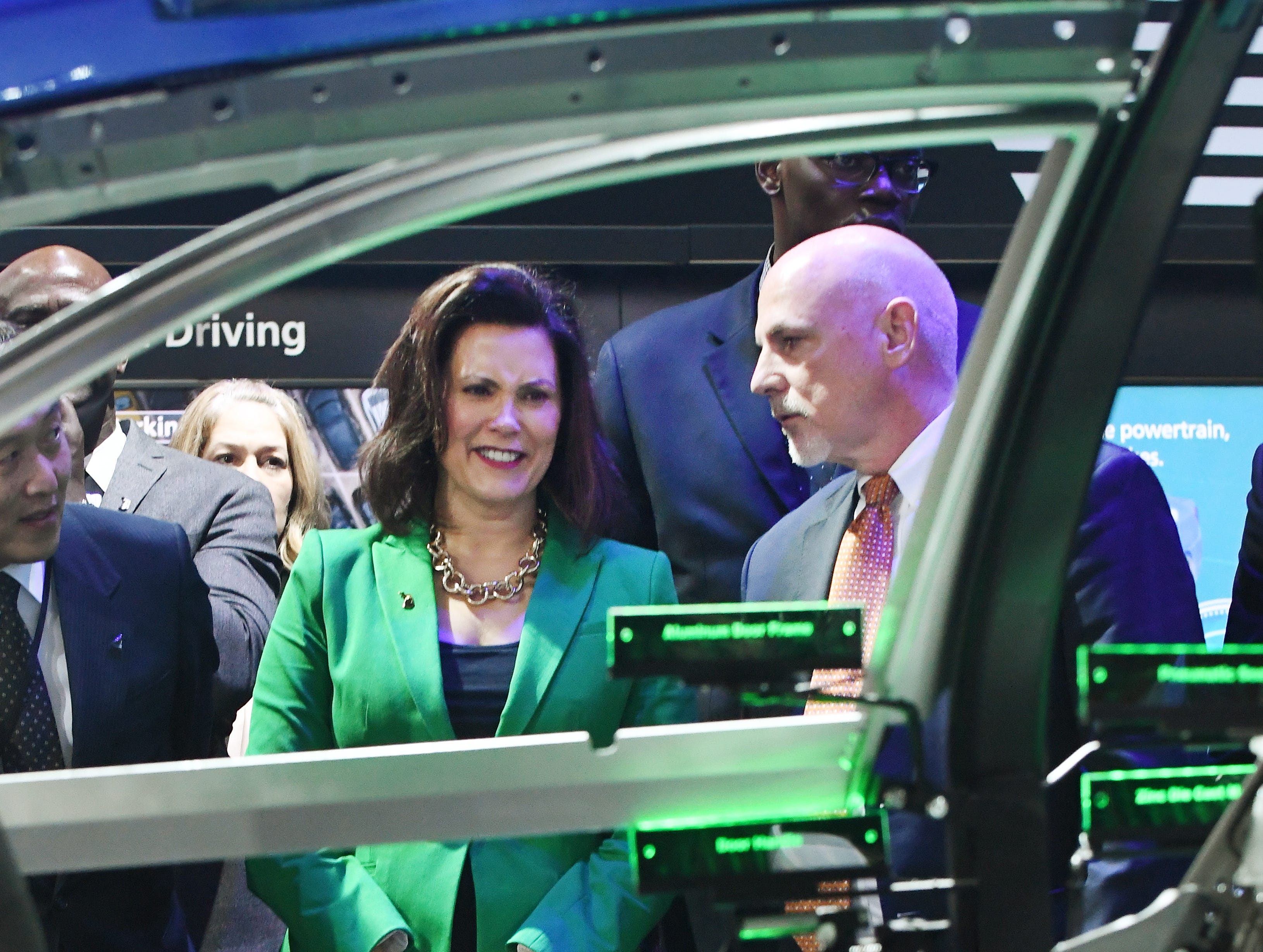 Michigan Governor Gretchen Whitmer and Aisin World Corporation President Scott Turpin during a tour of their display at North American International Auto Show.