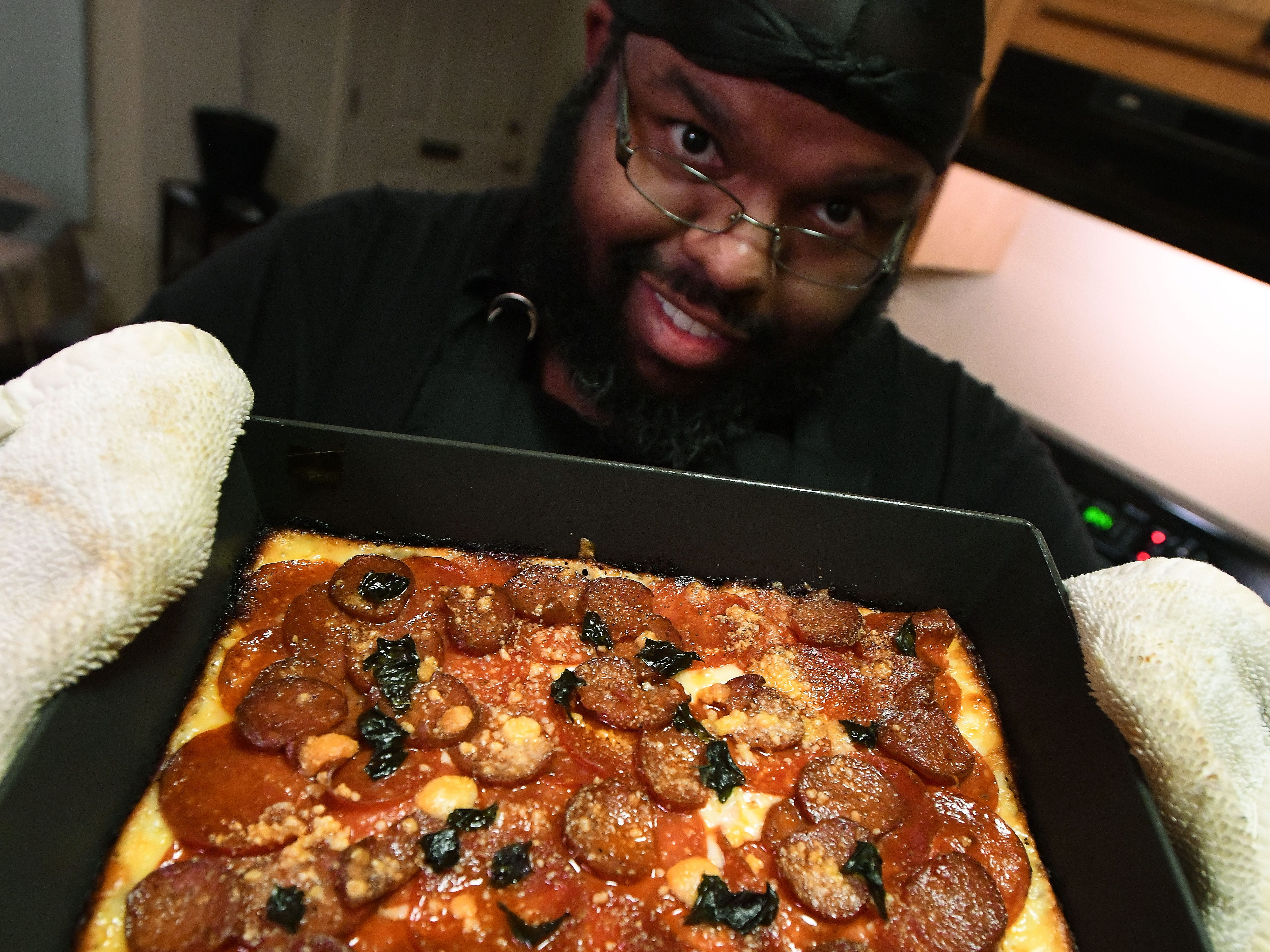 "Cliff Skighwalker displays his pepperoni, Gyulai sausage, basil and aged parmesan pizza on a hand-made crust with homemade sauce at his Pontiac home. Skighwalker hosts the web series ""Instachef"" which highlights cooks who sell their food primarily using Instagram. He is also an Instachef pizza chef, under the moniker ""Cliffs Pizza."""