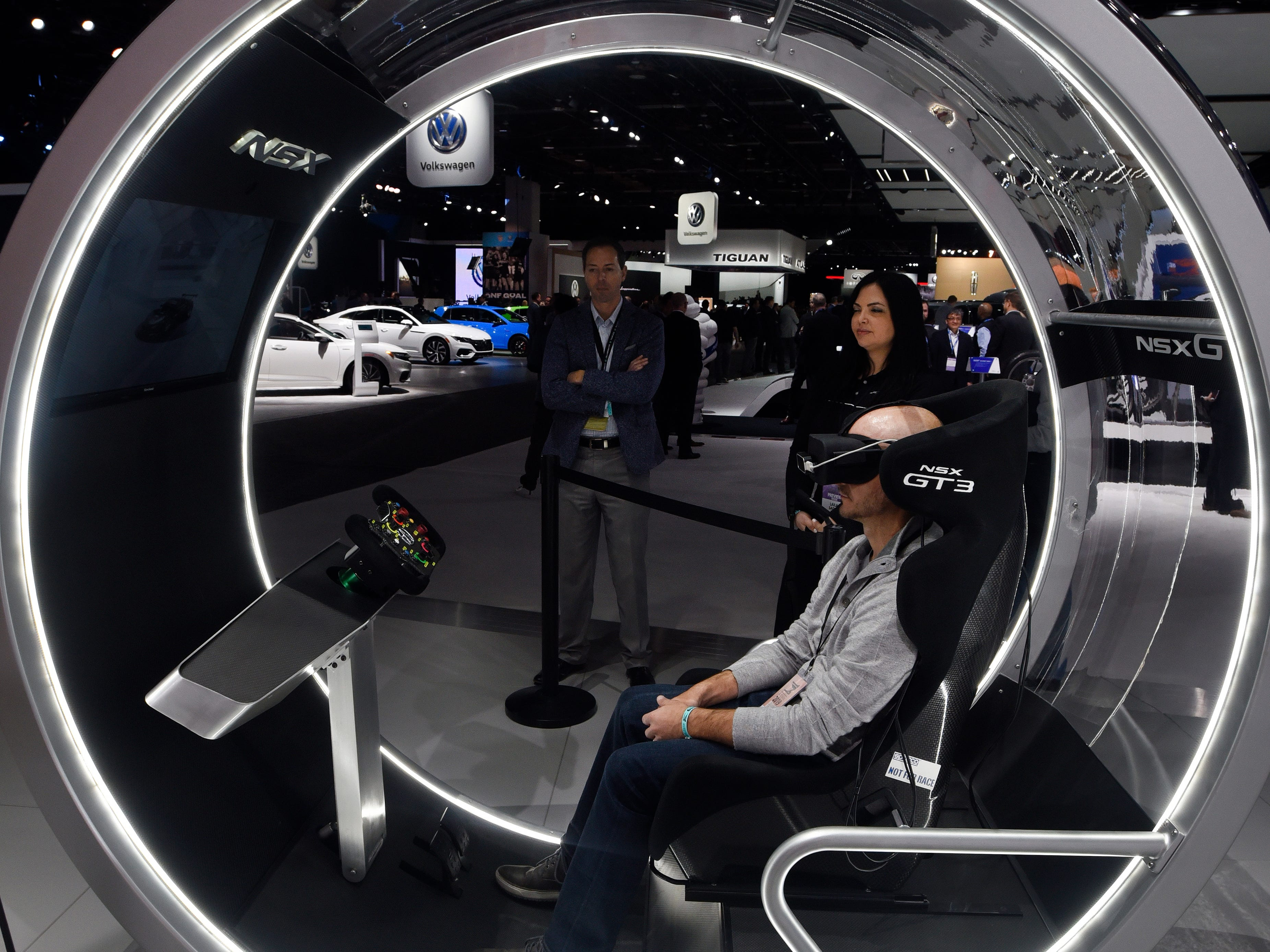 Darren Parker of American Express wears an Oculus at the Acura booth so he can get a virtual reality tour of the new Acura NSX sports car.