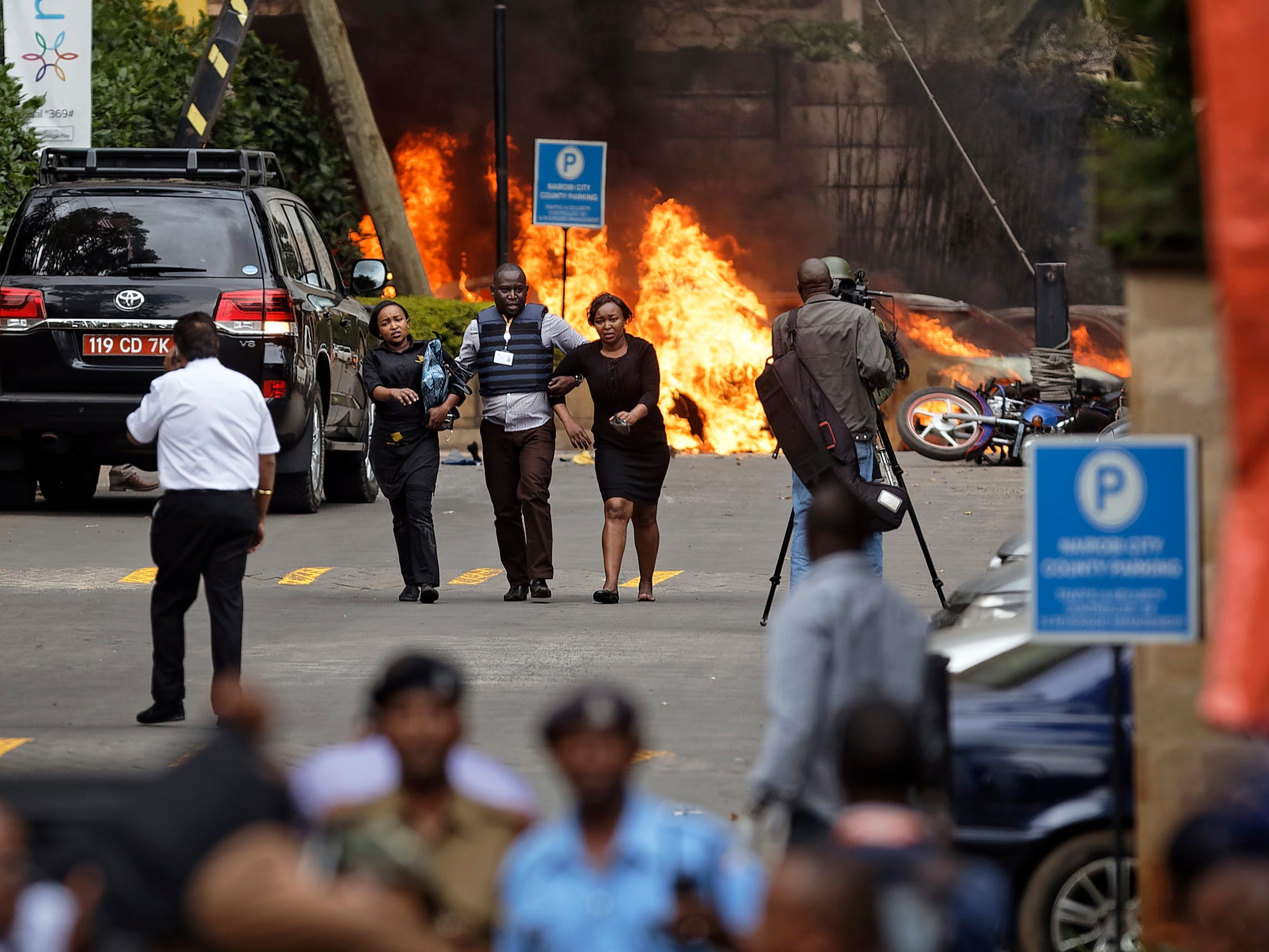 Security forces help civilians flee as cars burn behind at a hotel complex in Nairobi, Kenya Tuesday, January 15, 2019.