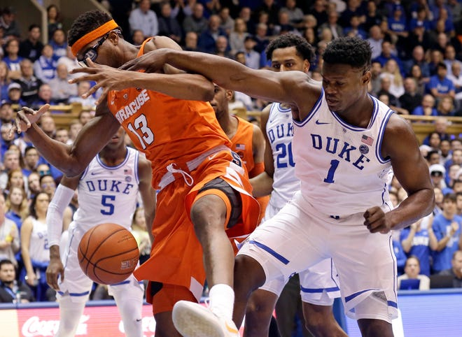 Duke's Zion Williamson (1) and Syracuse's Paschal Chukwu (13) chase a rebound during the first half Monday.