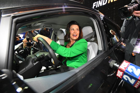 Michigan Gov. Gretchen Whitmer attracts a crowd of journalists as she sits in the drivers seat of a Chevy Bolt ev at the North American International Auto Show on Tuesday, January 15, 2019 at Cobo Center in Detroit. The show opens to the public on Saturday.