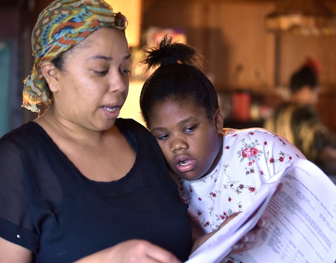 Kelly Hinojosa and her fifth-grade daughter, Ariel Lawson, 11, talk to each other as they look through an assessment test designed to help identify ADHD and other neurological conditions related to attention.  The evaluation may entitle Ariel and hundreds of other schoolchildren in Flint to special education services in the school district.