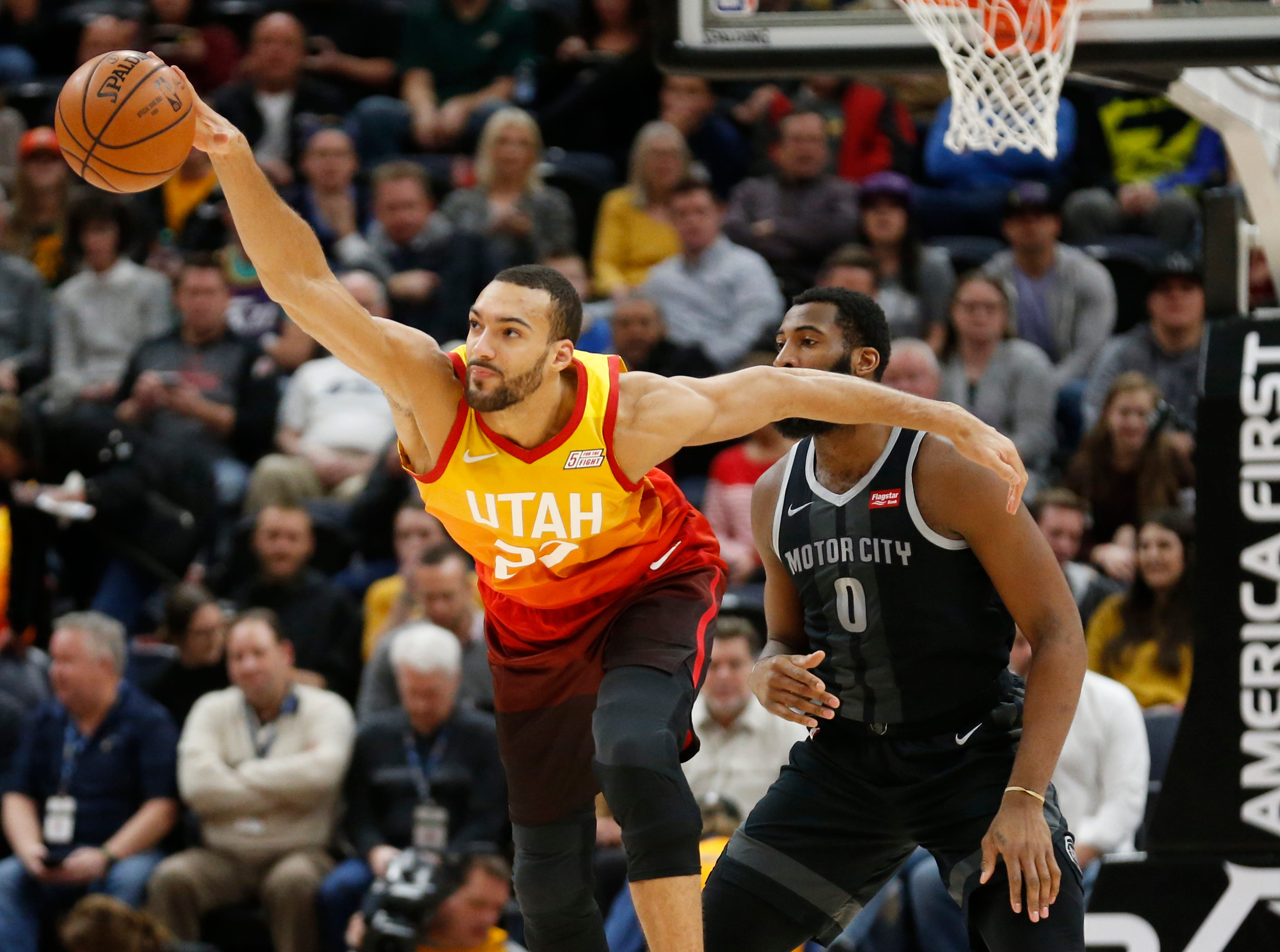 Utah Jazz center Rudy Gobert (27) reaches for the ball as Detroit Pistons center Andre Drummond (0) looks on during the first half of an NBA basketball game Monday, Jan. 14, 2019, in Salt Lake City. (AP Photo/Rick Bowmer)
