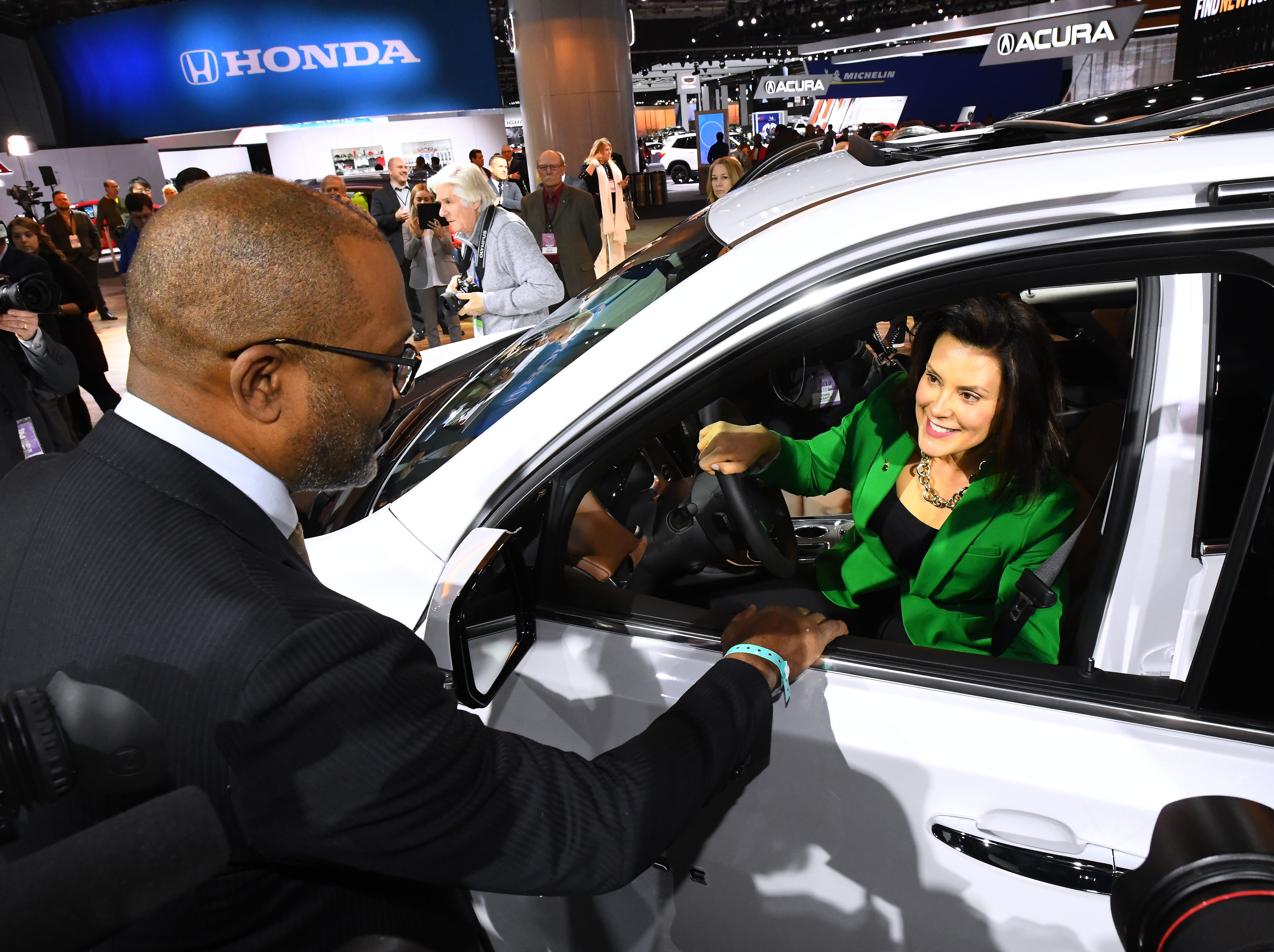 North America Manufacturing Vice President Gerald Johnson gives Michigan Governor Gretchen Whitmer  a look at the Chevrolet Travers in the General Motors display during a tour of the North American International Auto Show.