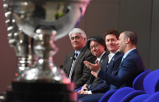 Behind the IndyCar trophy, from left, IndyCar President and CEO Mark Miles;  NTT Executive Vice President  Tsunehisa Okuno and IndyCar drivers Scott Dixon and Tony Kanaan speak at the announcement of a title sponsorship deal between IndyCar and NTT, a global information technology and communications company based in Japan, Tuesday at the Detroit auto show.