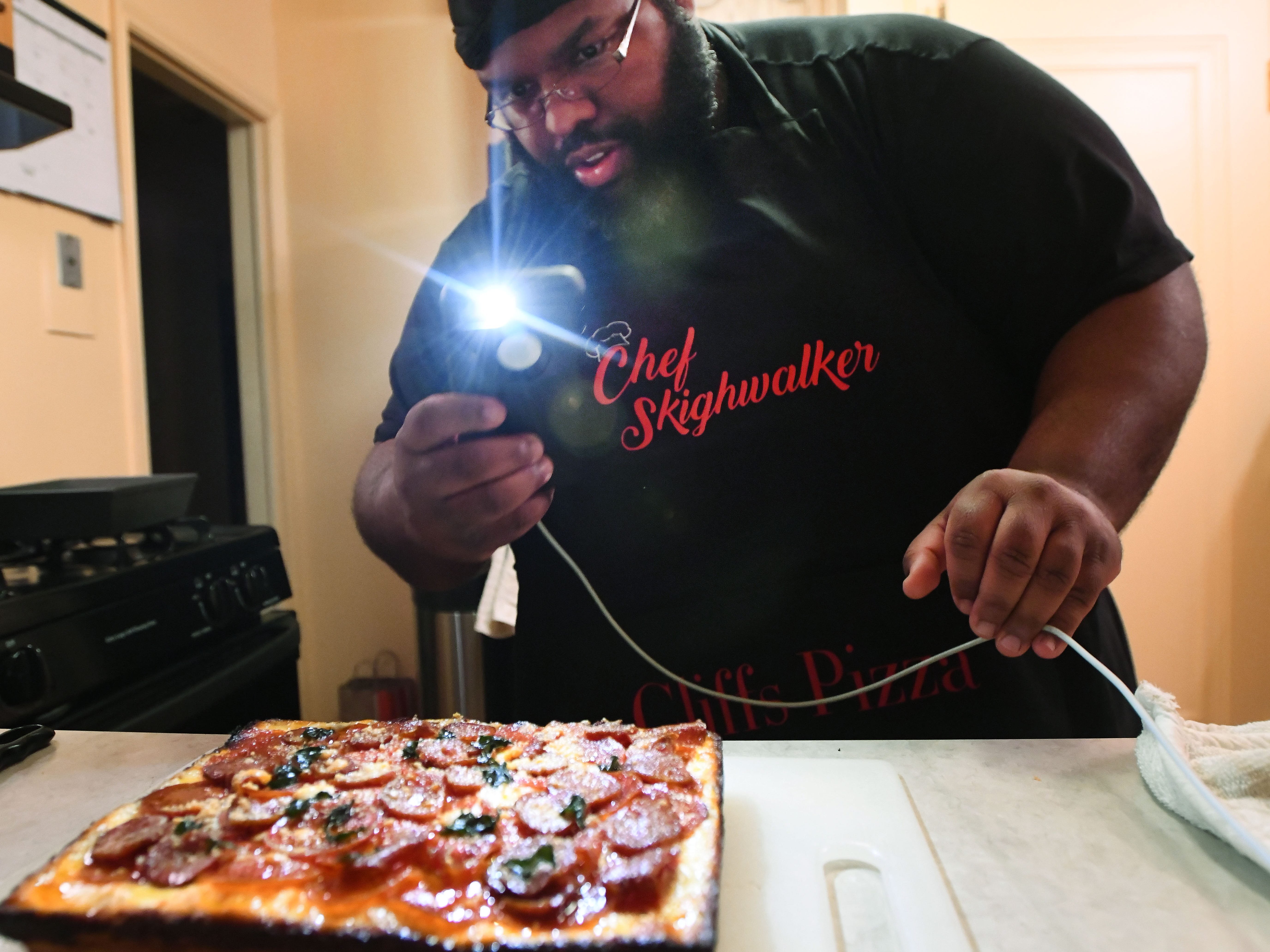 Cliff Skighwalker takes a picture of his pepperoni, Gyulai sausage, basil, aged parmesan pizza on a hand-made crust with homemade sauce at his Pontiac home for sale on Instagram.