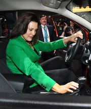 Michigan Governor Gretchen Whitmer looks over a Ford Ranger Sport truck as she tours Ford's display with Ford Motor Company's Curt Magleby at the North American International Auto Show.