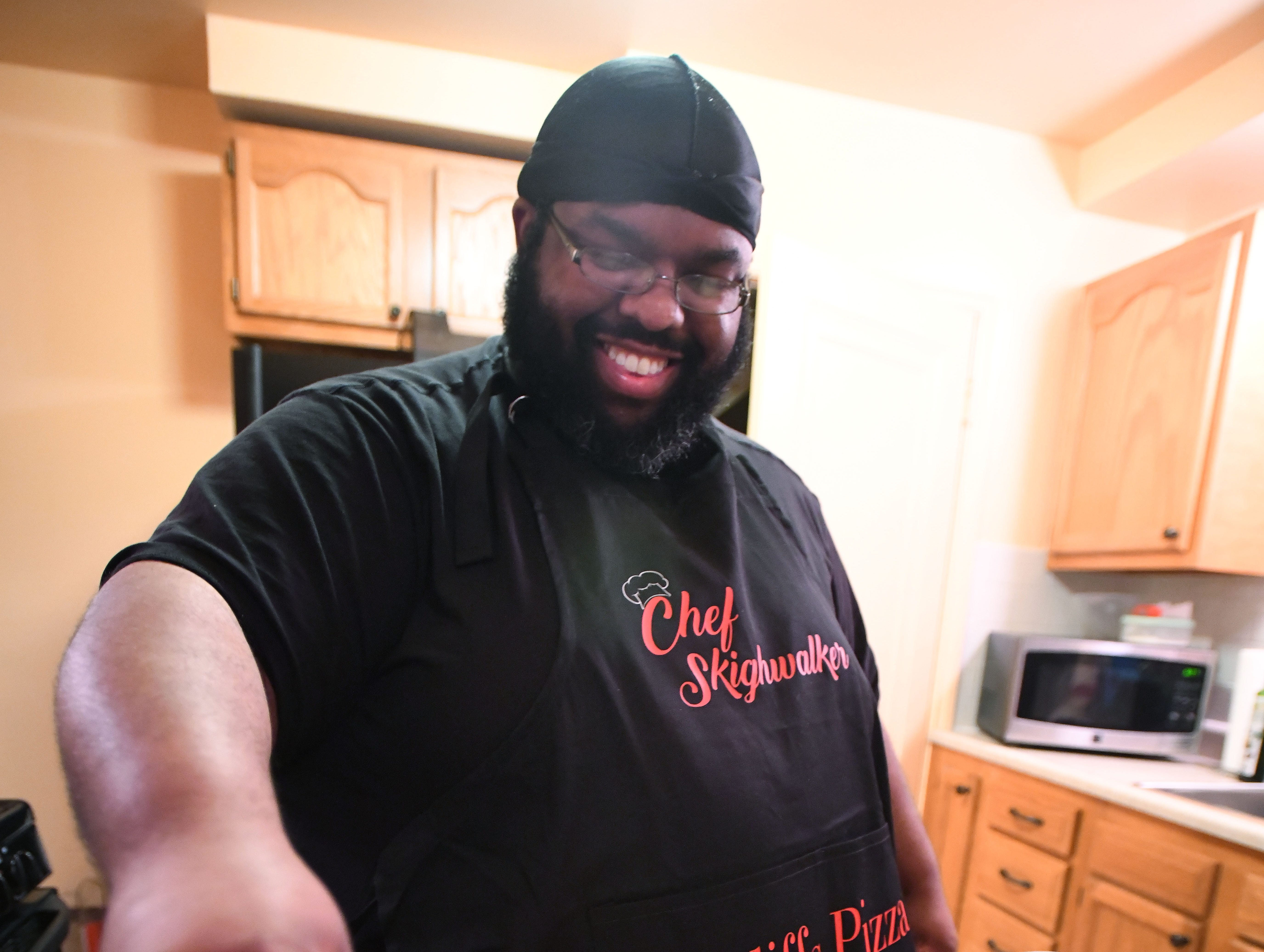 'Instachef' Cliff Skighwalker works on a couple pizzas in the kitchen of his home in Pontiac.