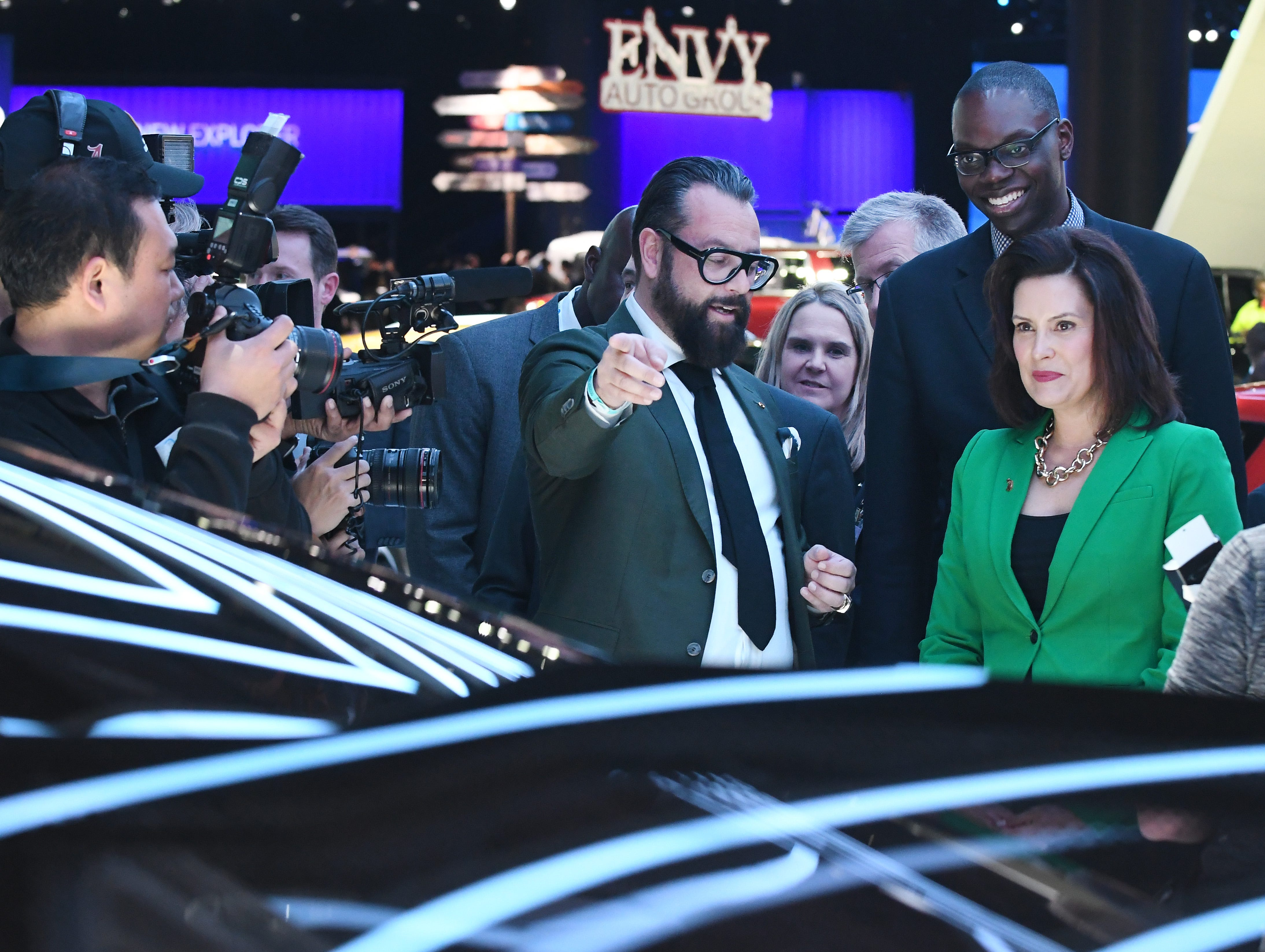 GAC Motor's Executive Design Directors Pontus Fontaeus shows Michigan Governor Gretchen Whitmer and Lieutenant Governor Garlin Gilchrist their display during a tour of the North American International Auto Show.